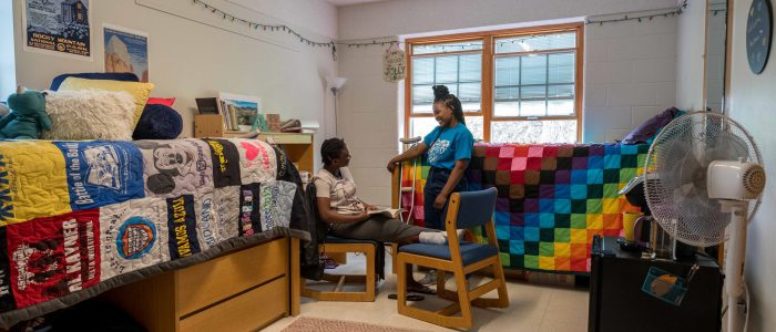 Two students talking with one another in a double room in DeWaters.