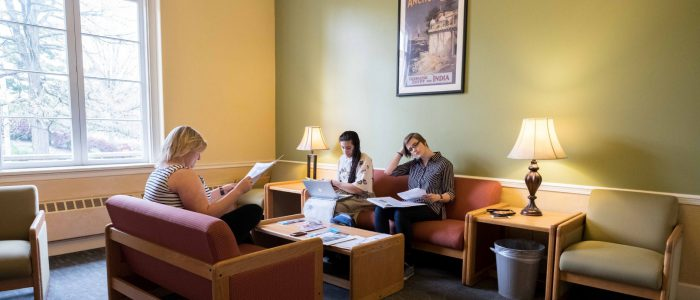 Students and a staff member sitting and reading in the Harmon lounge.